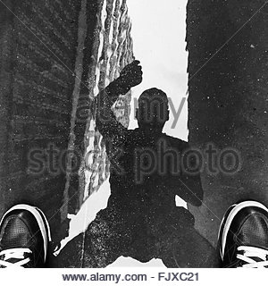 Low Section Of Man Standing On Puddle With Reflection - Stock Photo