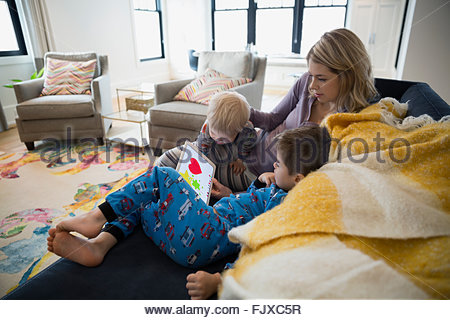 Mother and sons in pajamas using digital tablet - Stock Photo