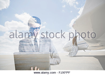 Digital composite businessman working on laptop near airplane - Stockfoto