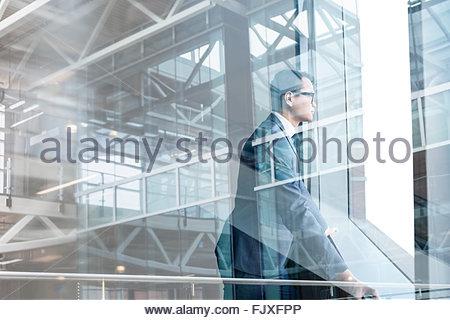 Digital composite businessman looking through modern window - Stockfoto