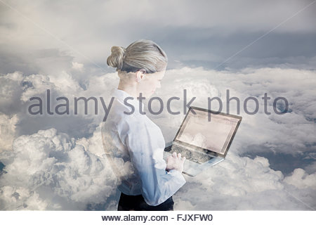 Digital composite businesswoman using laptop in clouds - Stockfoto