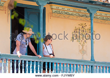 Two tourists standing on an old vintage balcony enjoying the beautiful view of the colonial village which is a Unesco - Stock Photo