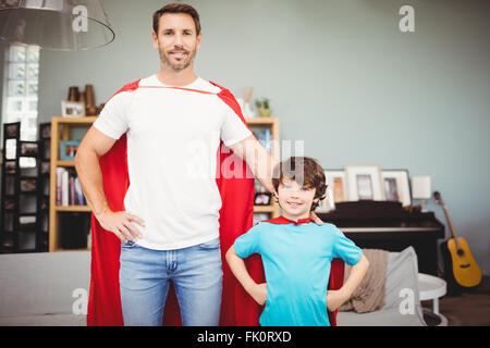 Portrait of smiling father and son in superhero costume - Stock Photo
