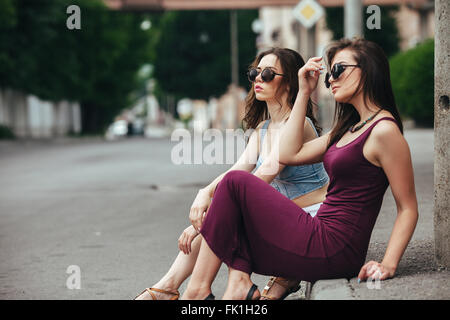 Two beautiful young girls posing in the city - Stock Photo