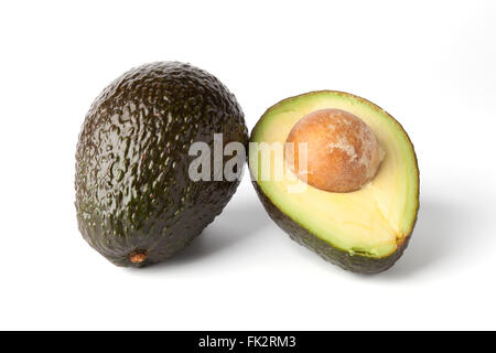 Whole and a half fresh avocado on white background - Stock Photo
