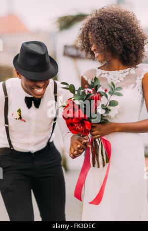 Stylish black groom in hat and his charming bride happily laughing on their wedding ceremony - Stock Photo