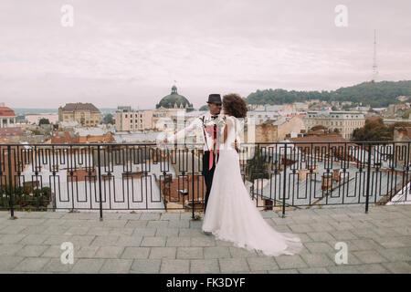 Happy black wedding couple softly hugging on the rooftop - Stock Photo
