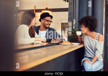 Happy young people sitting in a cafe and talking to each other. Group of young friends communicating and having - Stock Photo