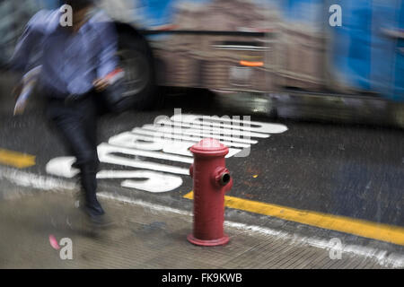 Man runs rain in the city center - Stock Photo