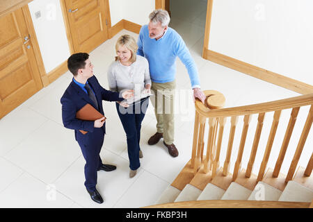 Realtor Showing Mature Couple Around House For Sale - Stock Photo