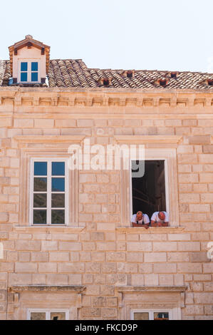 Chefs from the restaurant on the harbour front look down on tourists below in the old town of Dubrovnik, Croatia, - Stock Photo