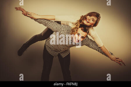 Love people and happiness oncept. Smiling young couple having fun, man giving piggyback ride to woman - Stock Photo