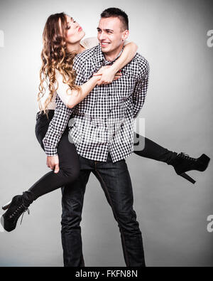 Love people and happiness oncept. Smiling young couple having fun, man giving piggyback ride to woman studio shot - Stock Photo