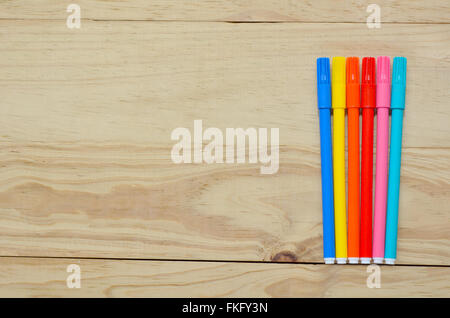 Coloring in pens on a wooden background. Creative lifestyle concept with copy space for text - Stock Photo