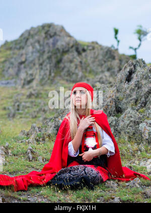 Beautiful blond woman in old-fashioned dress and red cloak sitting on the rocks - Stock Photo