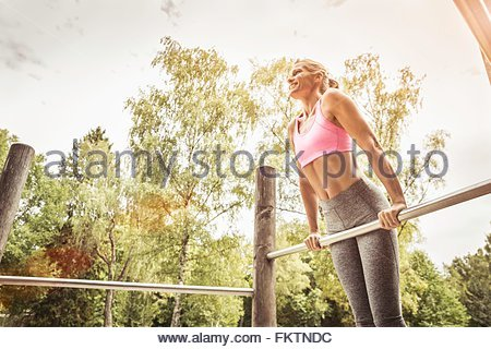 Mature women in park doing push ups on metal bar looking away smiling - Stock Photo