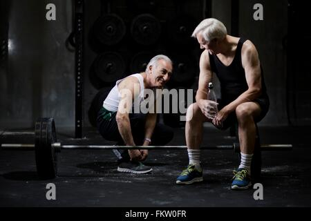 Senior men chatting and tying trainer laces in dark gym - Stock Photo