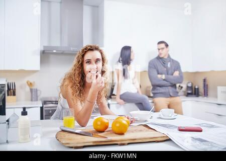 Portrait   young woman eating breakfast cereal at kitchen counter - Stock Photo