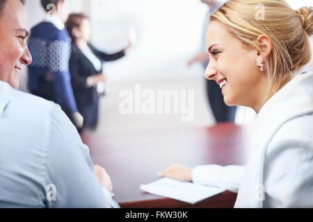 Over shoulder view   colleagues in conference room face to face smiling - Stock Photo