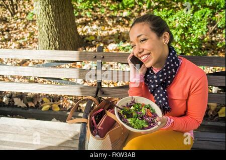 Young woman sitting on park bench chatting on smartphone whilst eating lunch - Stock Photo