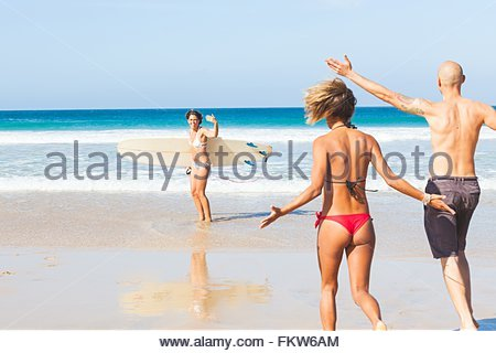 Young female surfer waving to friends on beach, El Cotillo, Fuerteventura, Spain - Stock Photo