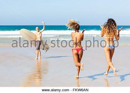 Male surfer waving to female friends on beach, El Cotillo, Fuerteventura, Spain - Stock Photo