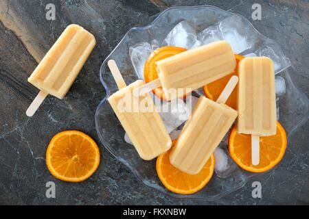 Homemade orange yogurt popsicles in an ice filled bowl with fresh fruit slices against a slate background - Stock Photo