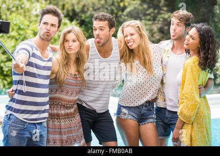 Group of friends taking a selfie near pool - Stock Photo