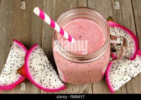 Pink raspberry, dragon fruit smoothie in jar mug on a wood background, downward view - Stock Photo