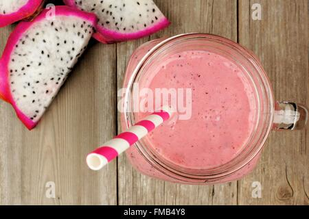 Pink raspberry, dragon fruit smoothie with fruit slices on a wood background, downward view - Stock Photo