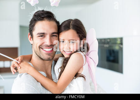 Portrait of cheerful father carrying daughter in fairy costume - Stockfoto