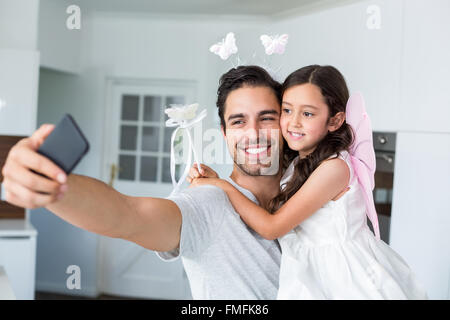 Smiling father taking self portrait with daughter in fairy costume - Stockfoto