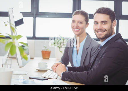 Happy business people working at computer at desk - Stockfoto