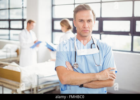 Portrait of doctor standing with arms crossed - Stock Photo