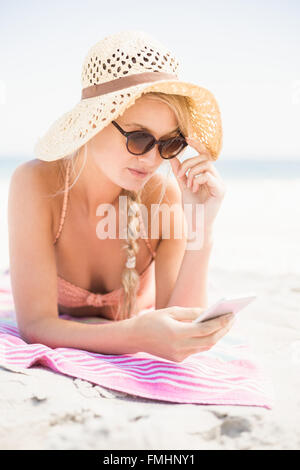 Pretty woman in bikini and sunglasses using mobile phone on the beach - Stock Photo