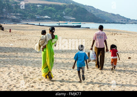 Local Indian family on beach at Anjuna Beach on Anjuna Market day,hippy,hippie,Goa,India,Asia, - Stock Photo