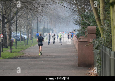 People enjoyed a bright but misty day on and around the Thames in London. The Thames Walk in Battersea Park is popular - Stock Photo