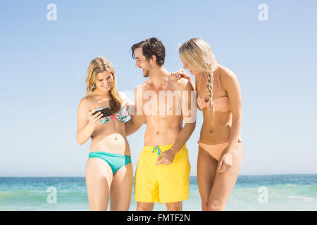 Young friends looking at mobile phone on the beach - Stockfoto