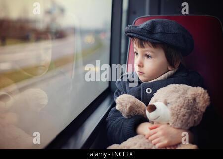 Sweet little child, preschool boy, riding in a bus, daytime, holding teddy bear - Stock Photo