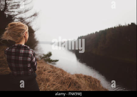 young woman standing on hill top admiring the beautiful view - Stock Photo