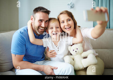 Family of three sitting on sofa and taking selfie - Stockfoto