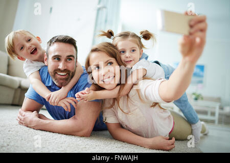 Happy young family taking selfie on the floor at home - Stockfoto