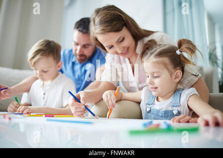 Mother helping her little daughter to draw - Stockfoto