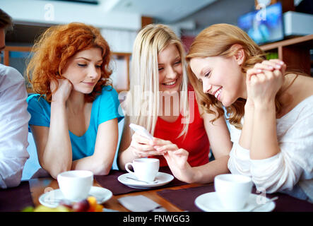 Happy teenage girls reading sms in cafe - Stock Photo