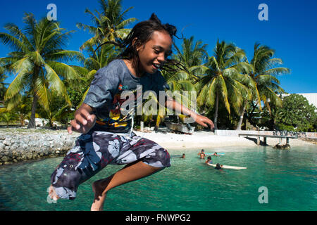 Beach of Rangiroa, Tuamotu Islands, French Polynesia, South Pacific. A kid playing and jumping in to the water. - Stock Photo