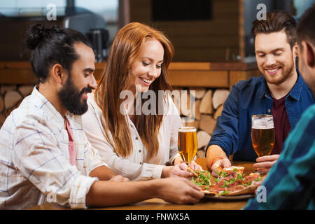 friends sharing pizza with beer at pizzeria - Stock Photo