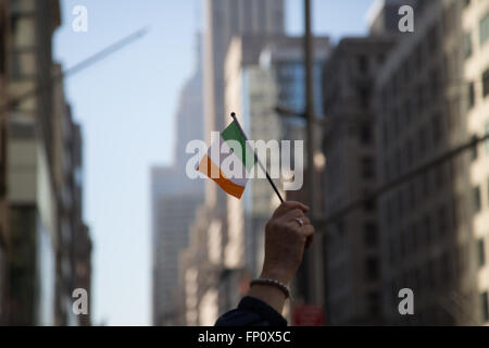 New York, USA. 17th Mar, 2016. A woman waves an Irish flag on 5th Avenue at the St. Patrick's Day Parade in New - Stock Photo