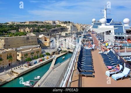 Mediterranean cruise ship liner sun deck of large tall modern ship port & city of Valletta Malta & passengers sunbathing - Stock Photo