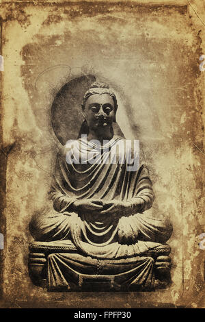 Vintage sepia toned seated meditating Buddha statue on a stained aged background with copy space in a conceptual - Stock Photo