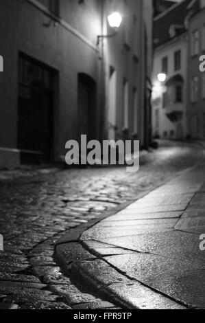Illuminated night city street of old european town. Blurred black and white image with focus on foreground pavement - Stock Photo